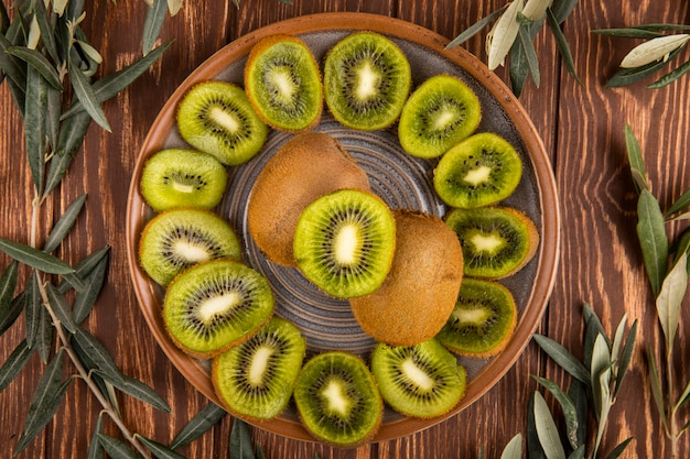 Top view of slices of kiwi fruit on a plate on wood