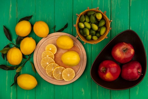 Top view of slices of lemons on a wooden kitchen board with red apples on a bowl with kinkans on a bucket with lemons isolated on a green wooden wall