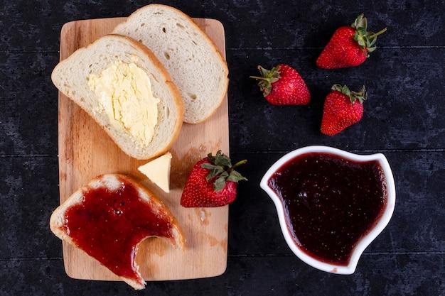 平面図のパンとバターのスライスとジャムとパンのスライスとボード上のイチゴとジャムの受け皿