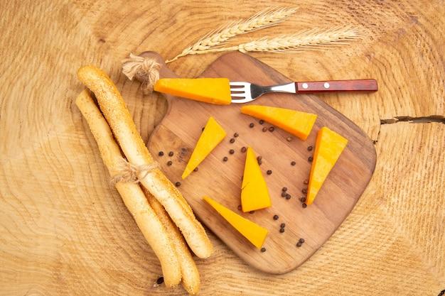 木製のテーブルの上のまな板小麦スパイク白パンのチーズとフォークの上面図スライス