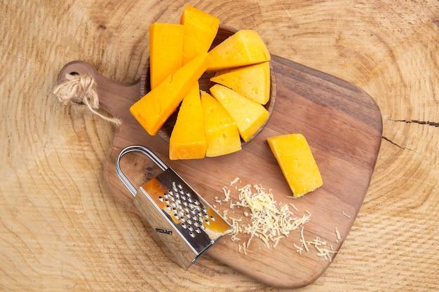 나무 테이블에 나무 커팅 보드에 그릇 상자 강판에 치즈의 상위 뷰 조각