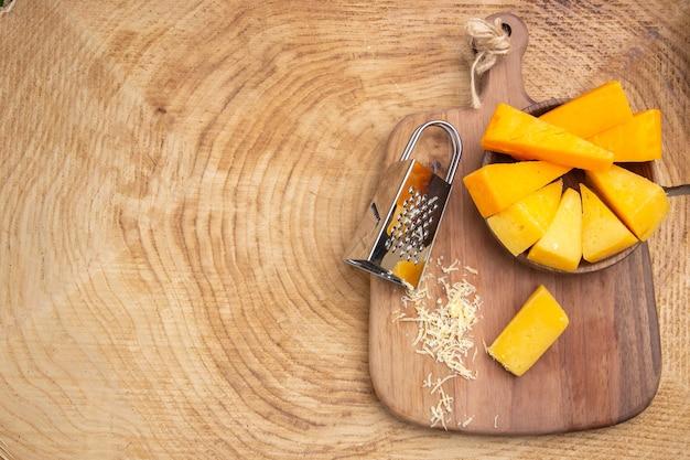 コピースペースと木製のテーブルのまな板に木製のボウルボックスおろし金でチーズの上面図スライス
