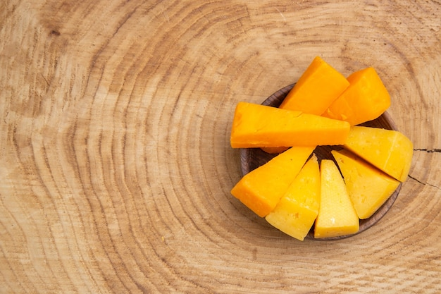 コピースペースと木製のテーブルの上の木製のボウルにチーズの上面図スライス