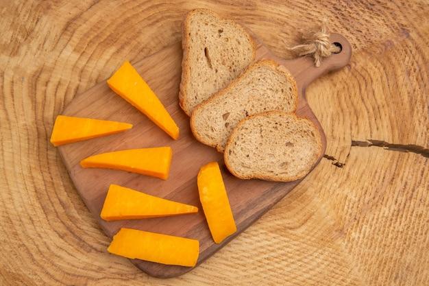 木製のテーブルのまな板の上のパンのチーズスライスの上面図スライス