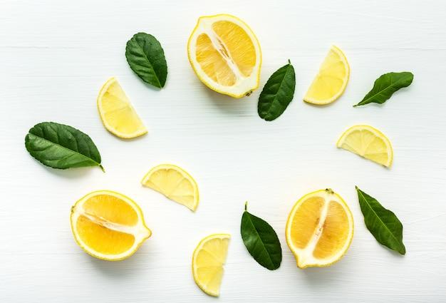 Куски взгляд сверху лимона и листьев лимона на белой таблице.