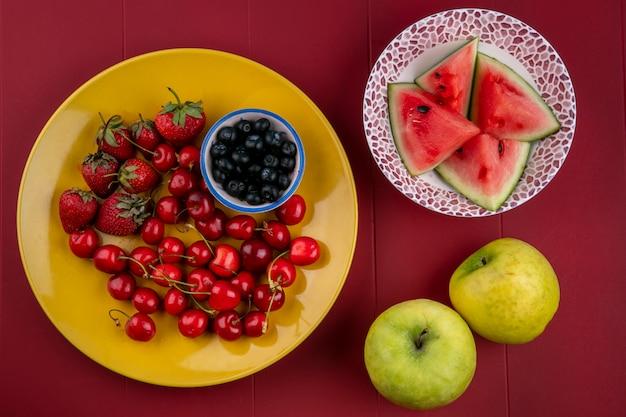 Вид сверху ломтики арбуза с черникой, клубникой, вишней на тарелке и яблоками на красном фоне