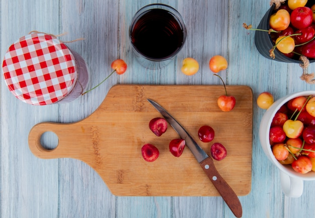 Top view of slices of red ripe cherry on a wood cutting board with a kitchen knife and rainier cherries glass of juice and jam in a glass jar on rustic