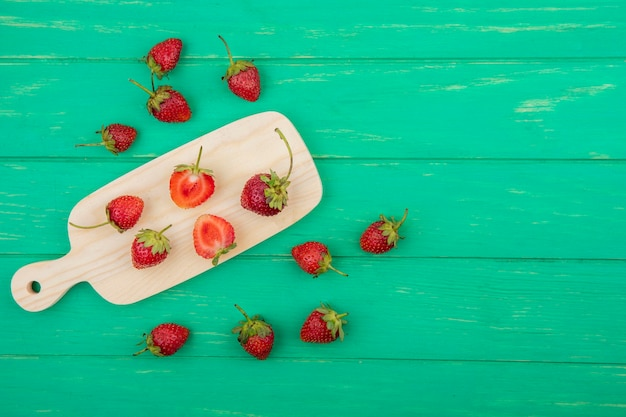 Top view of slices and whole strawberries on a wooden kitchen board on a green wooden background with copy space