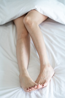 Top view of a slim woman legs. bare legs of a young woman sleeping on her bed at home.