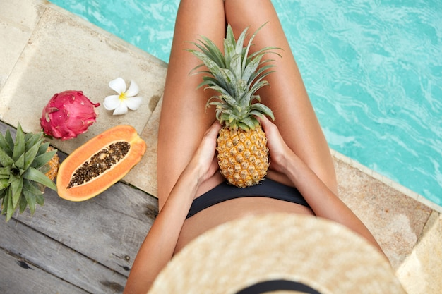 Top view of slim woman with tanned skin, sits near hotel pool enjoy vegan healthy diet food and eat tropical fruits, has summer pool party. female eats juicy exotic yield: pineapple and papya