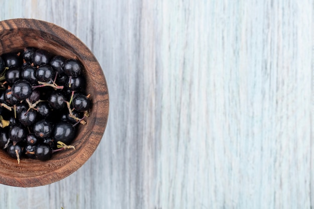 Top view of sloe berries in bowl on wooden surface
