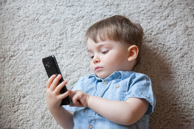 Top view of small boy playing with a telephone instead of actual baby toys.