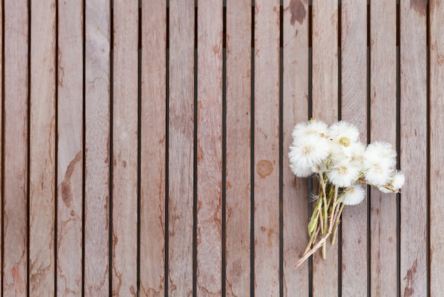 Top view of small bunch of summer dandelion flowers on wooden table