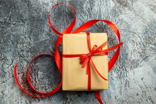 Top view small gift tied with red ribbon on dark isolated surface