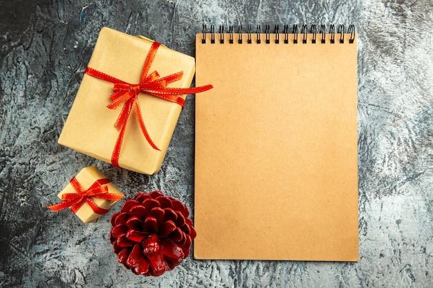 Вид сверху небольшой подарок, перевязанный красной лентой, тетрадь, цветная сосновая шишка на серой поверхности