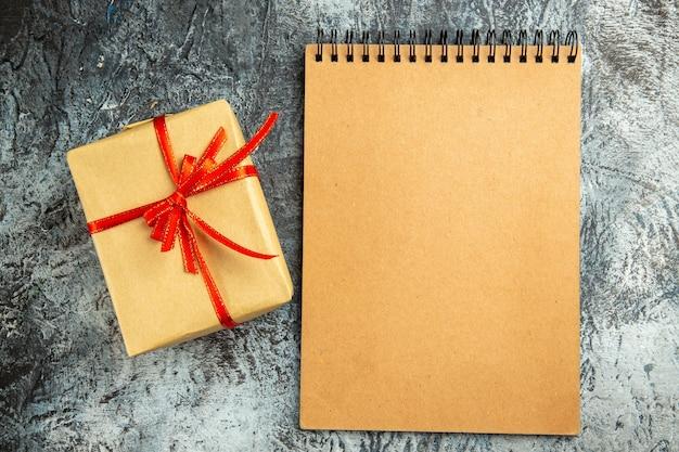 Vista dall'alto piccolo regalo legato con taccuino con nastro rosso su superficie grigia
