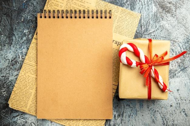 Вид сверху небольшой подарок, перевязанный блокнотом с красной лентой на газете на серой поверхности
