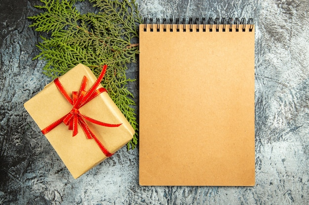 Vista dall'alto piccolo regalo legato con ramo di pino quaderno nastro rosso su superficie grigia