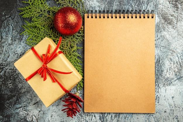 Vista dall'alto piccolo regalo legato con nastro rosso quaderno ramo di pino albero di natale giocattoli su sfondo grigio