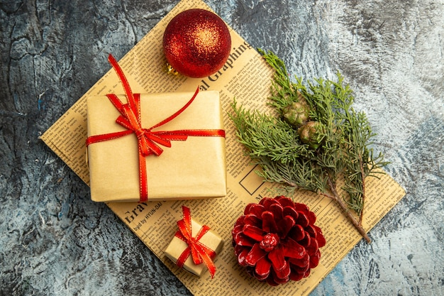 어두운 표면에 신문에 빨간 리본 빨간 공 소나무 가지와 함께 묶인 상위 뷰 작은 선물