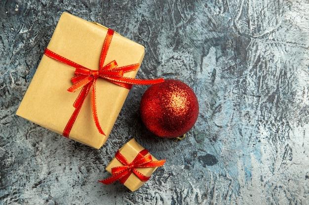 Вид сверху небольшой подарок, перевязанный красной лентой, красный елочный шар на темном фоне