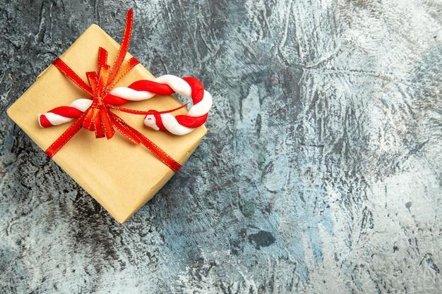 Vista dall'alto piccolo regalo legato con nastro rosso caramelle natalizie su superficie grigia