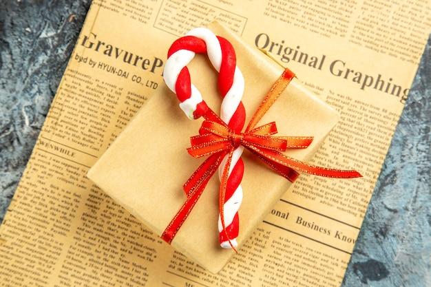 Vista dall'alto piccolo regalo legato con nastro rosso caramelle natalizie su giornale su superficie grigia