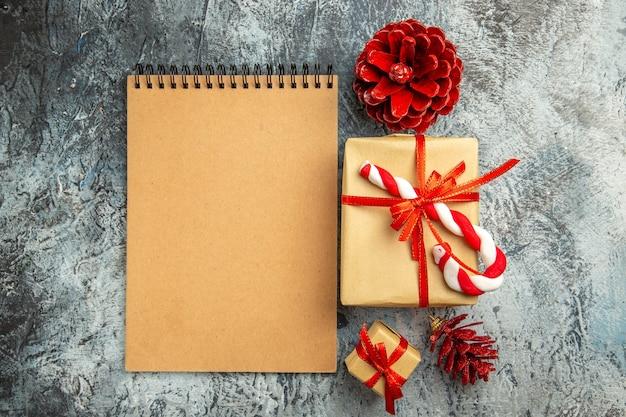 Vista dall'alto piccolo regalo legato con pigne di taccuino di caramelle di natale nastro rosso su superficie grigia