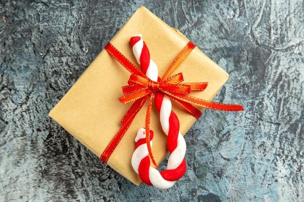 회색 배경에 빨간 리본 크리스마스 사탕으로 묶인 상위 뷰 작은 선물