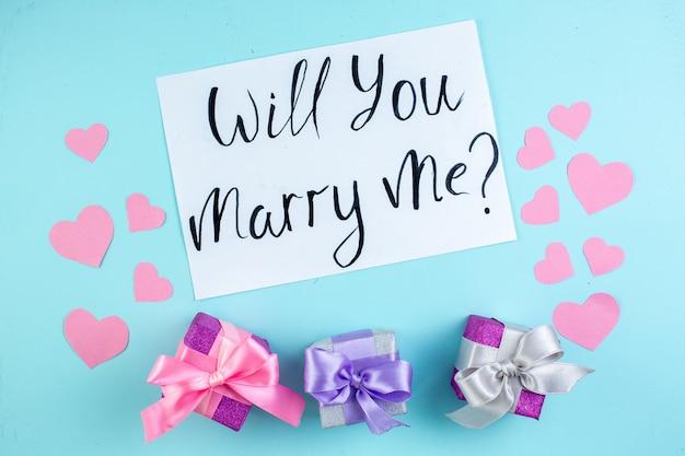 Вид сверху маленькие подарки розовые сердечки наклейки ты выйдешь за меня замуж написано на бумаге на синем фоне