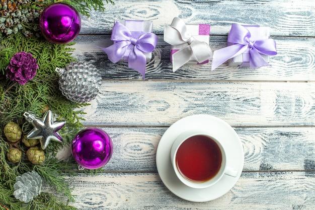 Vista dall'alto piccoli regali albero di natale giocattoli rami di abete una tazza di tè su superficie di legno