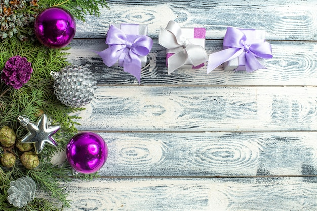 Vista dall'alto piccoli regali albero di natale giocattoli rami di abete su sfondo di legno spazio libero