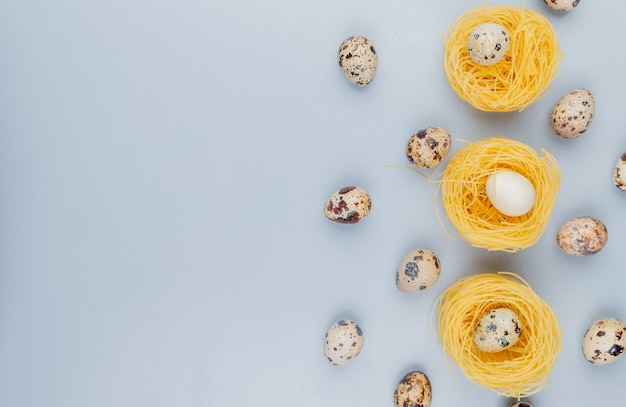 Top view of small quail eggs with cream colored shells on a nest on a white background with copy space