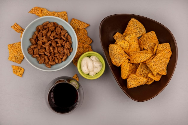 Top view of small rye rusks on a bowl with delicious chips with a glass of cola with sauce