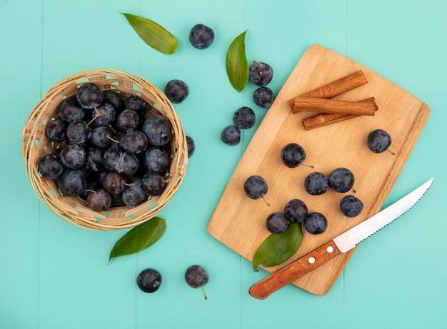 Vista dall'alto delle piccole prugnole di frutta nerastre acide su un secchio con prugnole su una tavola da cucina in legno con bastoncini di cannella con coltello su sfondo blu