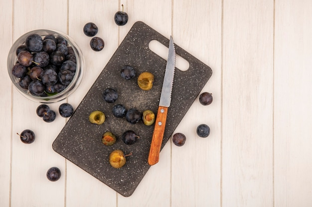 Top view of the small sour blue-black fruit sloes on a glass jar with slices of sloes on a kitchen cutting board with knife on a white wooden background