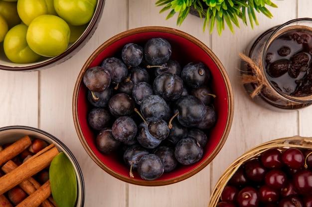 Vista dall'alto delle piccole prugnole di frutta blu-nere aspre su una ciotola rossa con una marmellata di fragole con ciliegie rosse su un secchio su un fondo di legno bianco