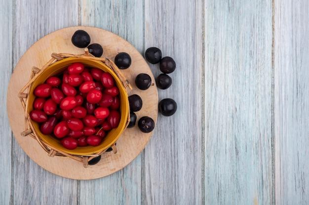 Vista dall'alto di piccole bacche di corniolo rosso acido su un secchio su una tavola di cucina in legno su un fondo di legno grigio con lo spazio della copia