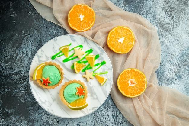 平面図小さなタルトとグリーンペストリークリームとレモンスライスをプレートにベージュのショールカットオレンジを暗いテーブルに空きスペースあり