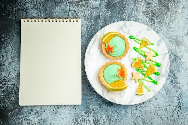 Вид сверху маленькие пирожные с кремом из зеленого теста и ломтиком лимона на тарелке, блокнот на темном столе