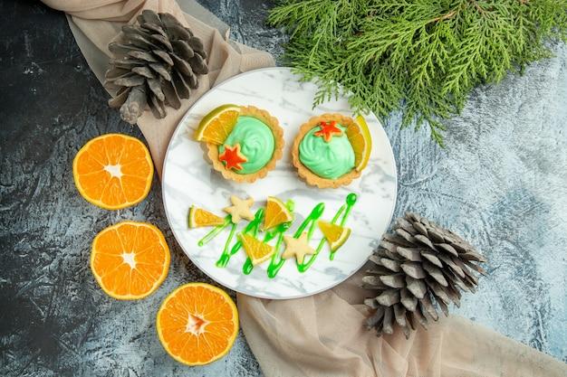 Вид сверху маленькие пирожные с кремом из зеленого теста и ломтиком лимона на тарелке на бежевой шали, разрезанные апельсины, шишки на темном столе