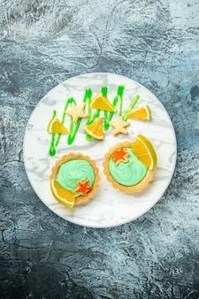 Вид сверху маленькие пирожные с кремом из зеленого теста и ломтиком лимона на тарелке на темном столе свободное место