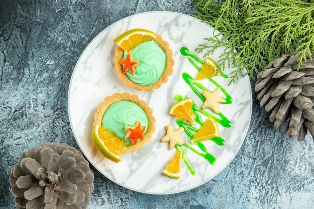 Вид сверху маленькие пирожные с кремом из зеленого теста и ломтиком лимона на тарелке сосновая ветка на темном столе