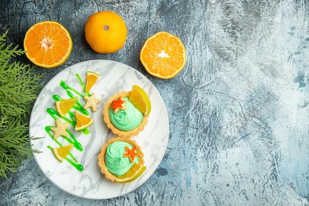 Vista dall'alto piccole crostate con crema pasticcera verde e fetta di limone sul piatto tagliate le arance sul tavolo scuro copia spazio