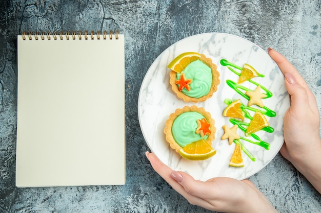 Vista dall'alto piccole crostate con crema pasticcera verde e fetta di limone sul piatto in donna mani notebook sul tavolo grigio