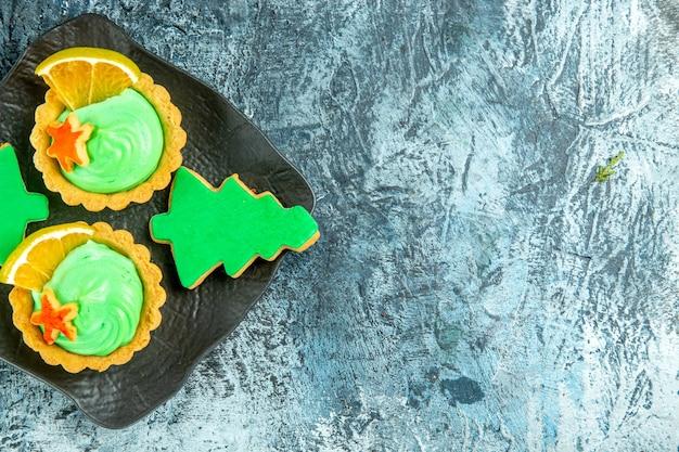 Vista dall'alto piccole torte con biscotti di natale crema pasticcera verde sulla banda nera sulla tavola grigia con lo spazio della copia