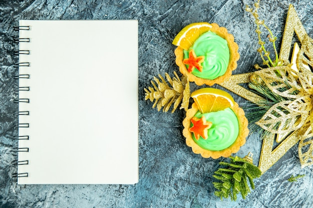 Top view small tarts with green pastry cream xmas ornaments notebook on grey table