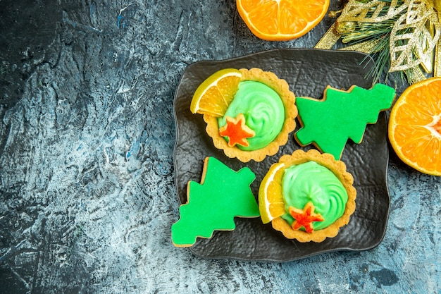 검은 접시에 녹색 과자 크림 크리스마스 트리 비스킷과 상위 뷰 작은 타르트 크리스마스 장식 회색 테이블 여유 공간에 오렌지를 잘라
