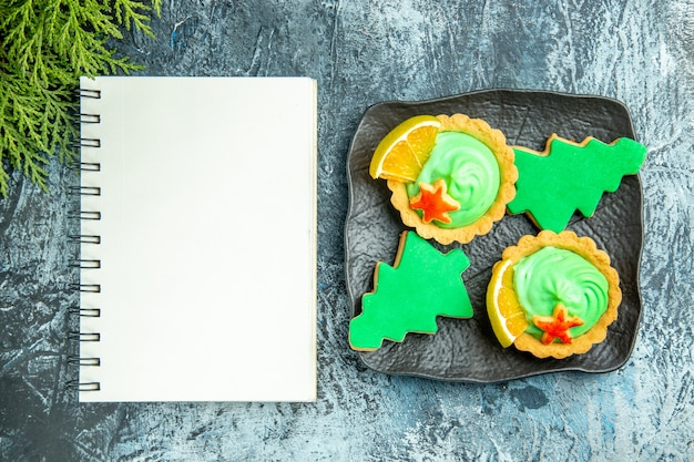 Top view small tarts xmas tree biscuits on black plate notepad on grey table