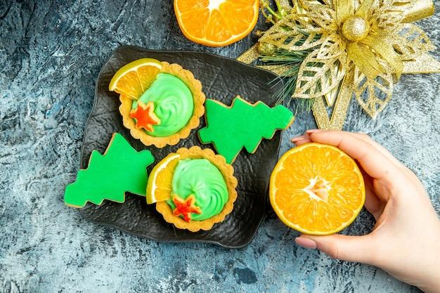 Vista dall'alto piccole torte biscotti dell'albero di natale sulla piastra nera ornamento di natale tagliato arancione in mano femminile sul tavolo grigio